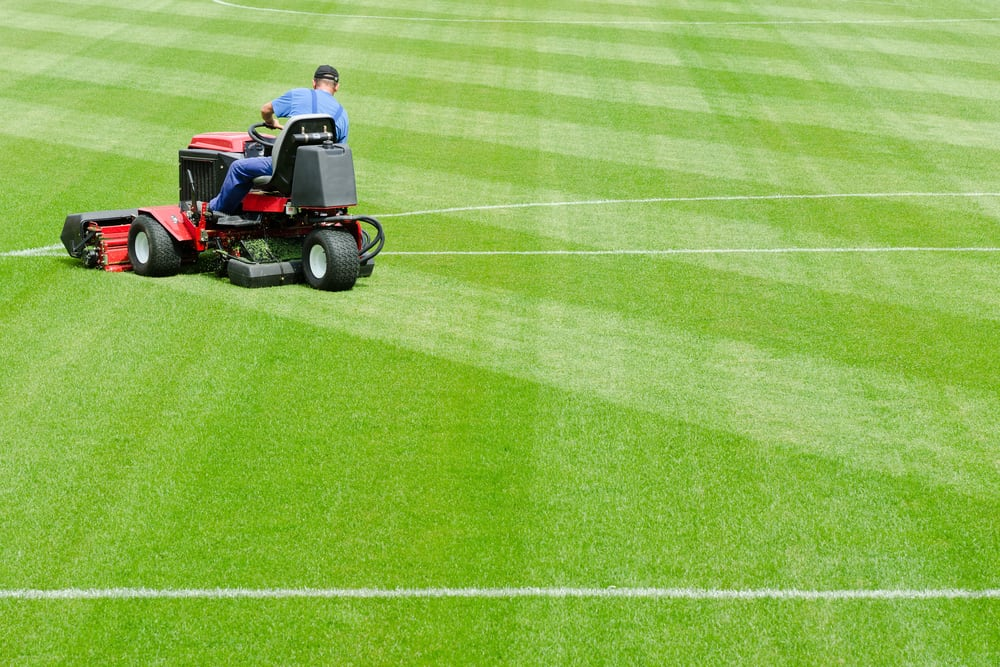 playing field grounds keeper on mower